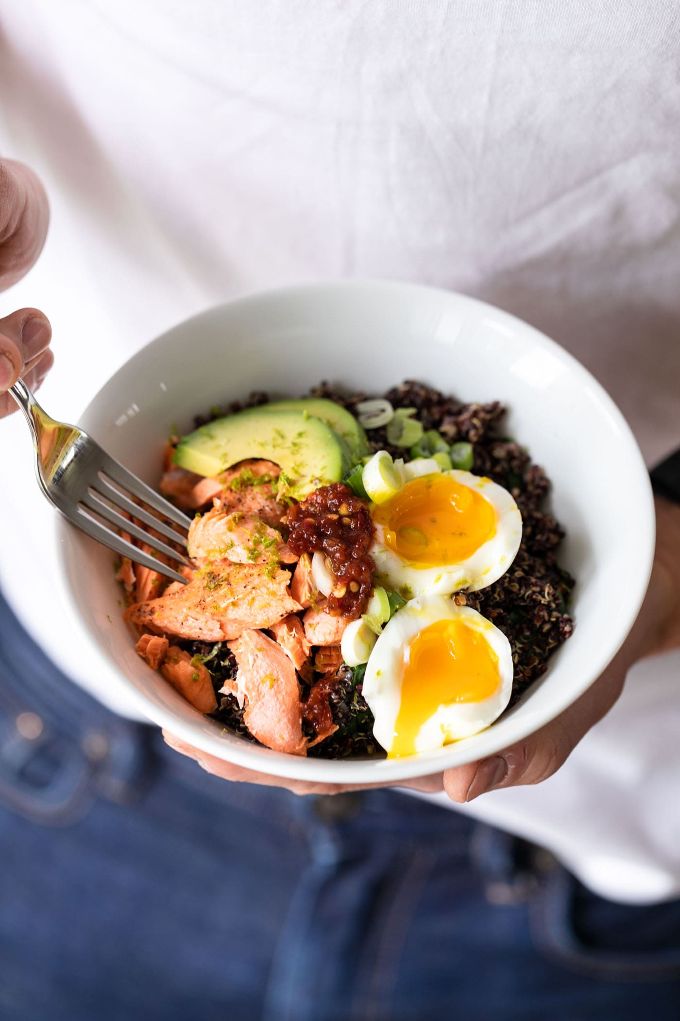 Hands holding white bowl filled with quinoa, avocado, salmon, and a slice egg with a fork taking a piece with white shirt in background