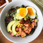 Top down view of salmon bowl topped with avocado and jammy eggs all on wood surface with toppings set around