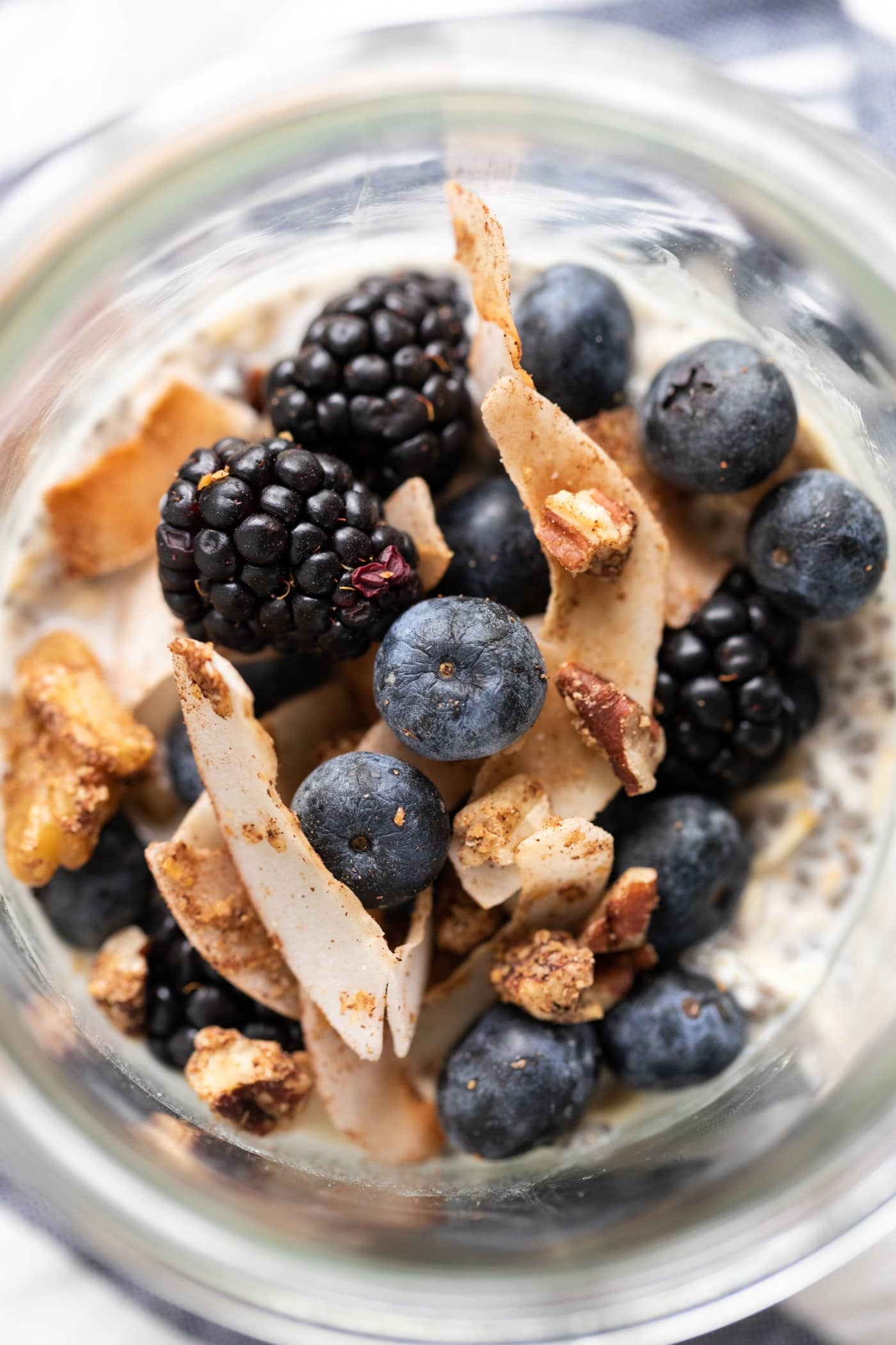 Blueberries, blackberries, and granola sitting on top of container of overnight oats
