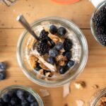 Top down view of vegan overnight oats in glass container with blueberries and granola on top all on wood surface