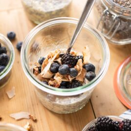 Vegan overnight oats sitting in glass container topped with granola and blueberries all on wood surface with extra toppings spread around