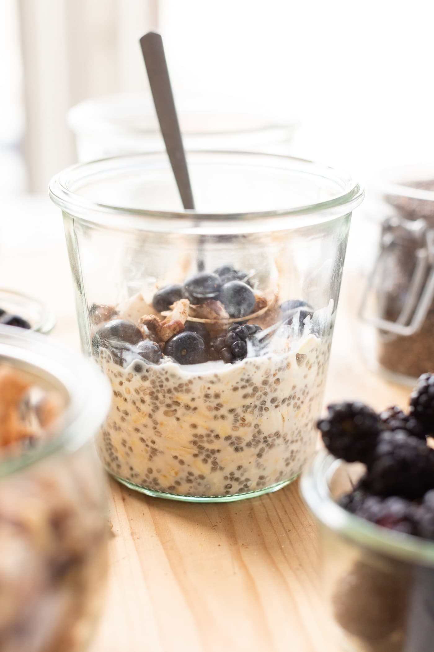 Glass container filled with overnight oats and topped with blueberries and granola with a spoon all on wood surface