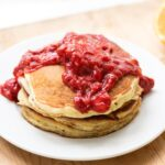 Stack of buttermilk pancakes topped with red rhubarb strawberry sauce with sliced orange in background all on wood surface