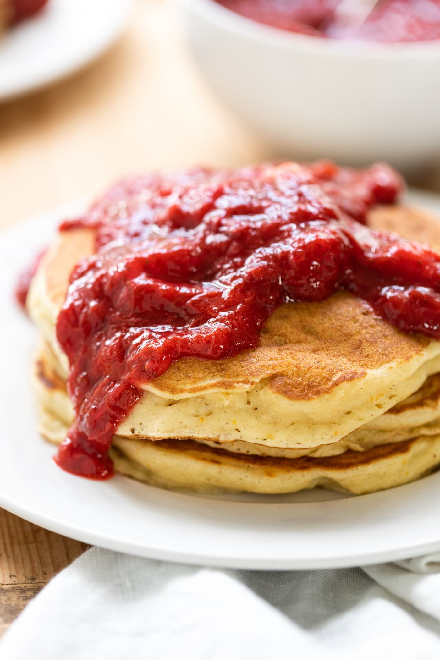 Three buttermilk pancakes sitting on white plate smothered with rhubarb strawberry sauce with linen towel in front all on wood surface