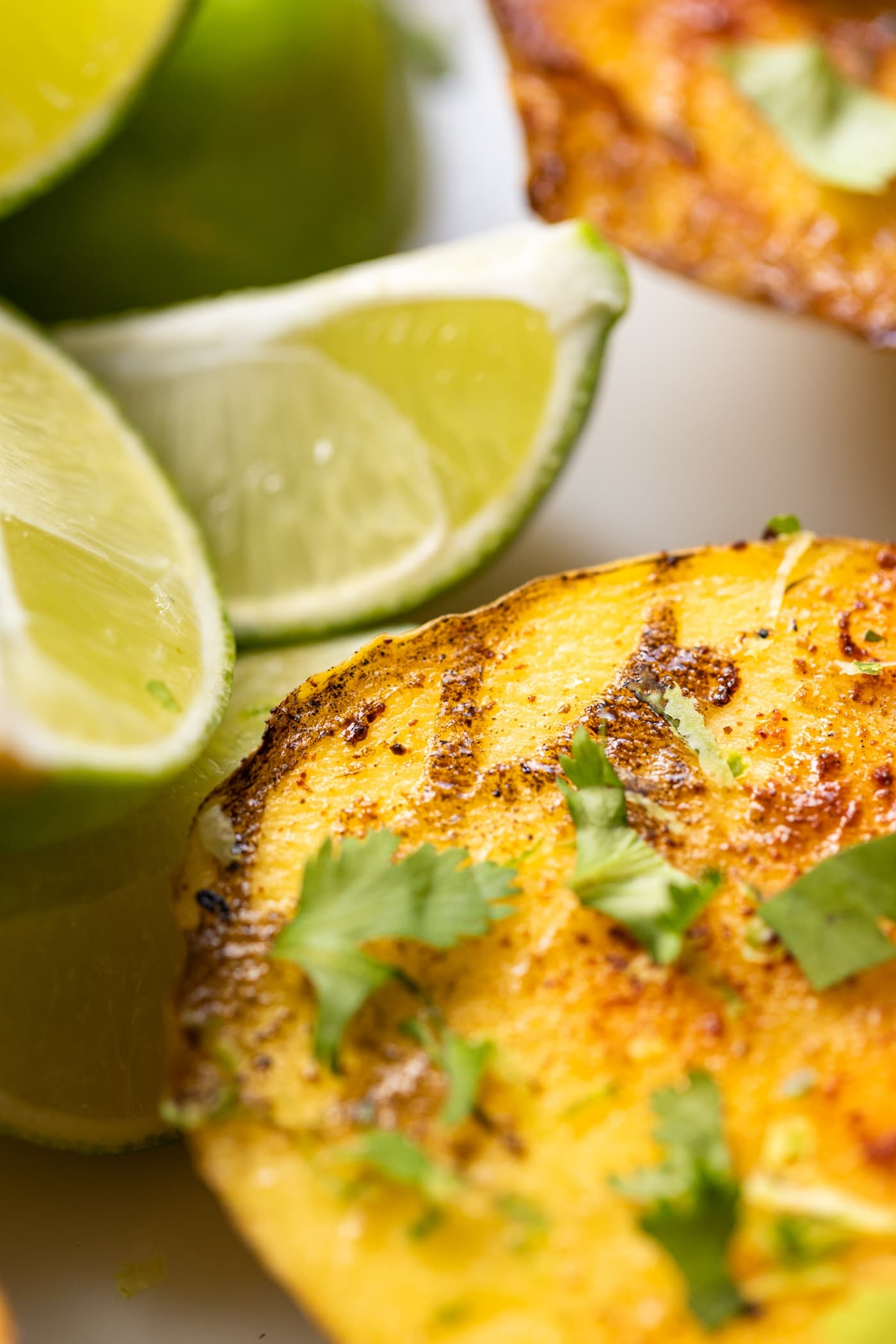 Close up view of mango sitting on white surface with limes and topped with cilantro and spices with grill marks