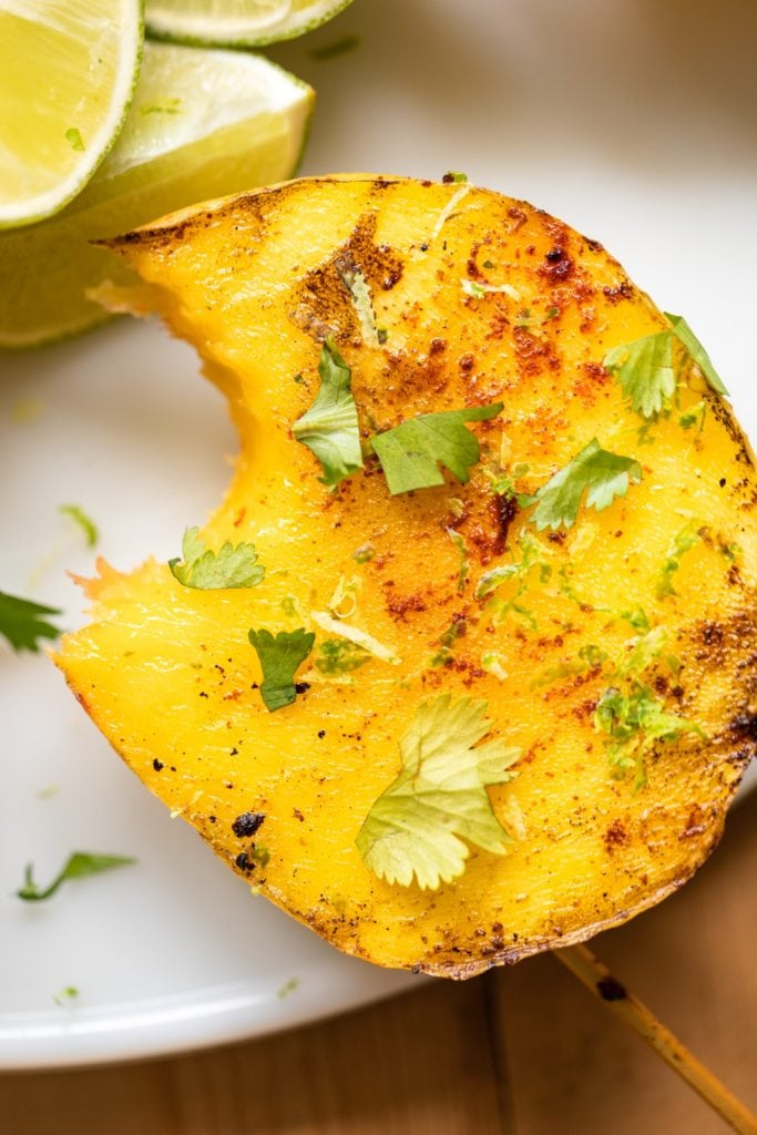 Mango sitting on white serving platter with bite taken out and topped with cilantro and spices