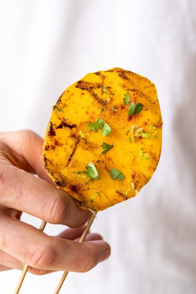 Hand holding grilled chili mango topped with cilantro and spices with two sticks coming out of bottom in front of white t-shirt
