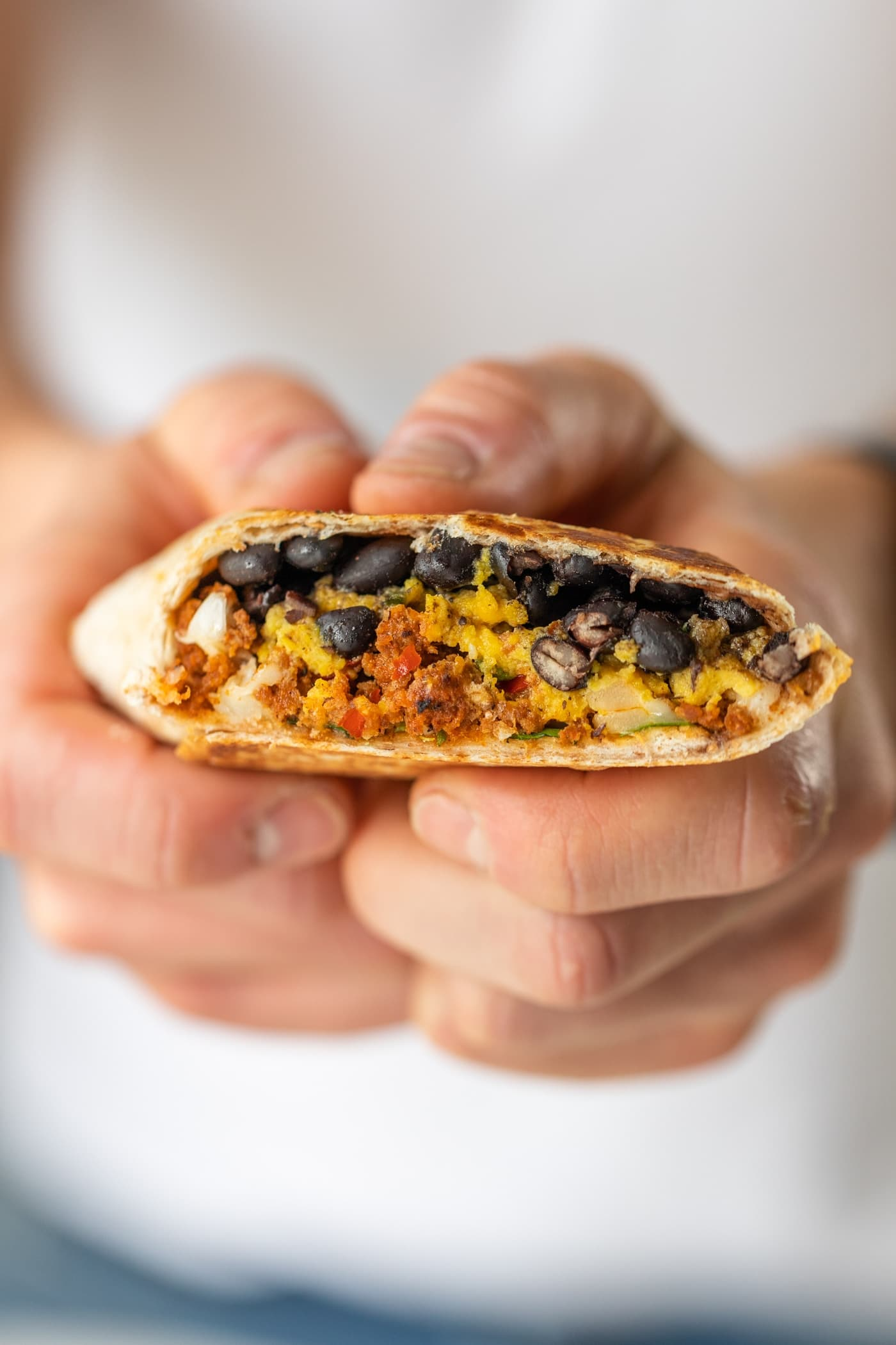 Two hands holding southwestern breakfast burrito with layers of black beans, chorizo, cheese, and eggs with white shirt in background