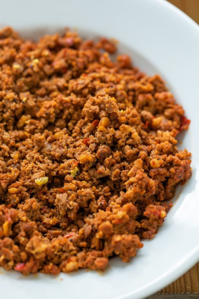 Cooked chorizo sausage sitting in white bowl on wood surface