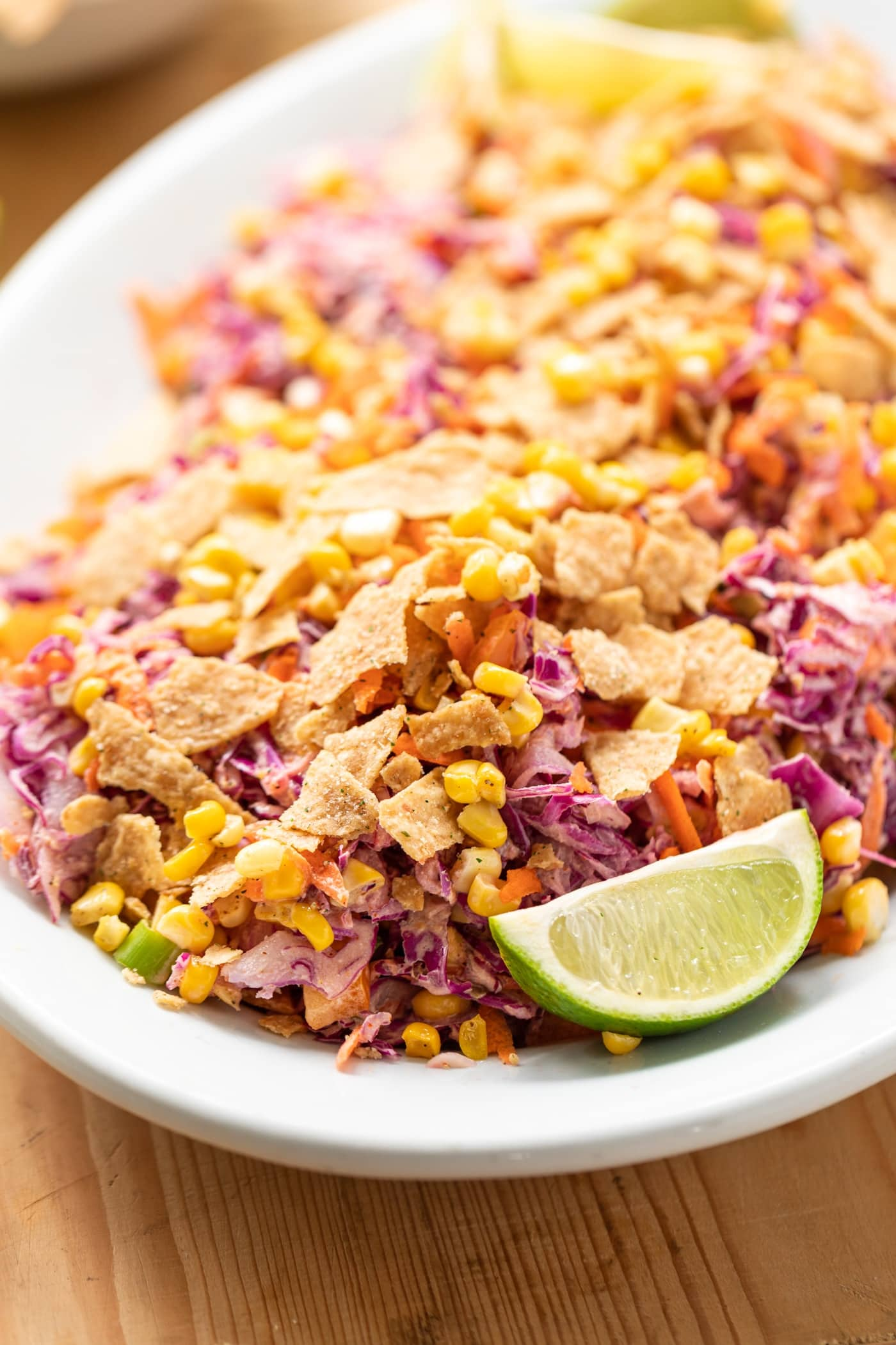 Tex-Mex coleslaw served on white serving platter topped with crushed tortilla chips and lime wedge all on wood surface