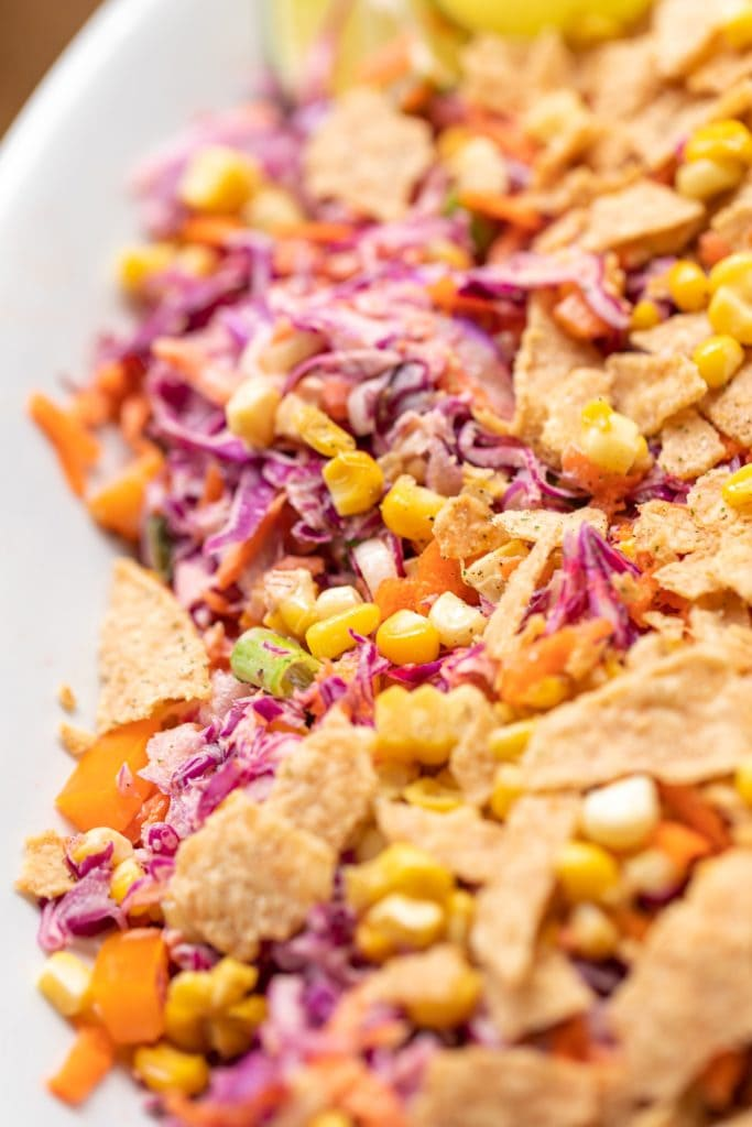 Coleslaw created from red cabbage served with corn and tortilla chips on white serving platter