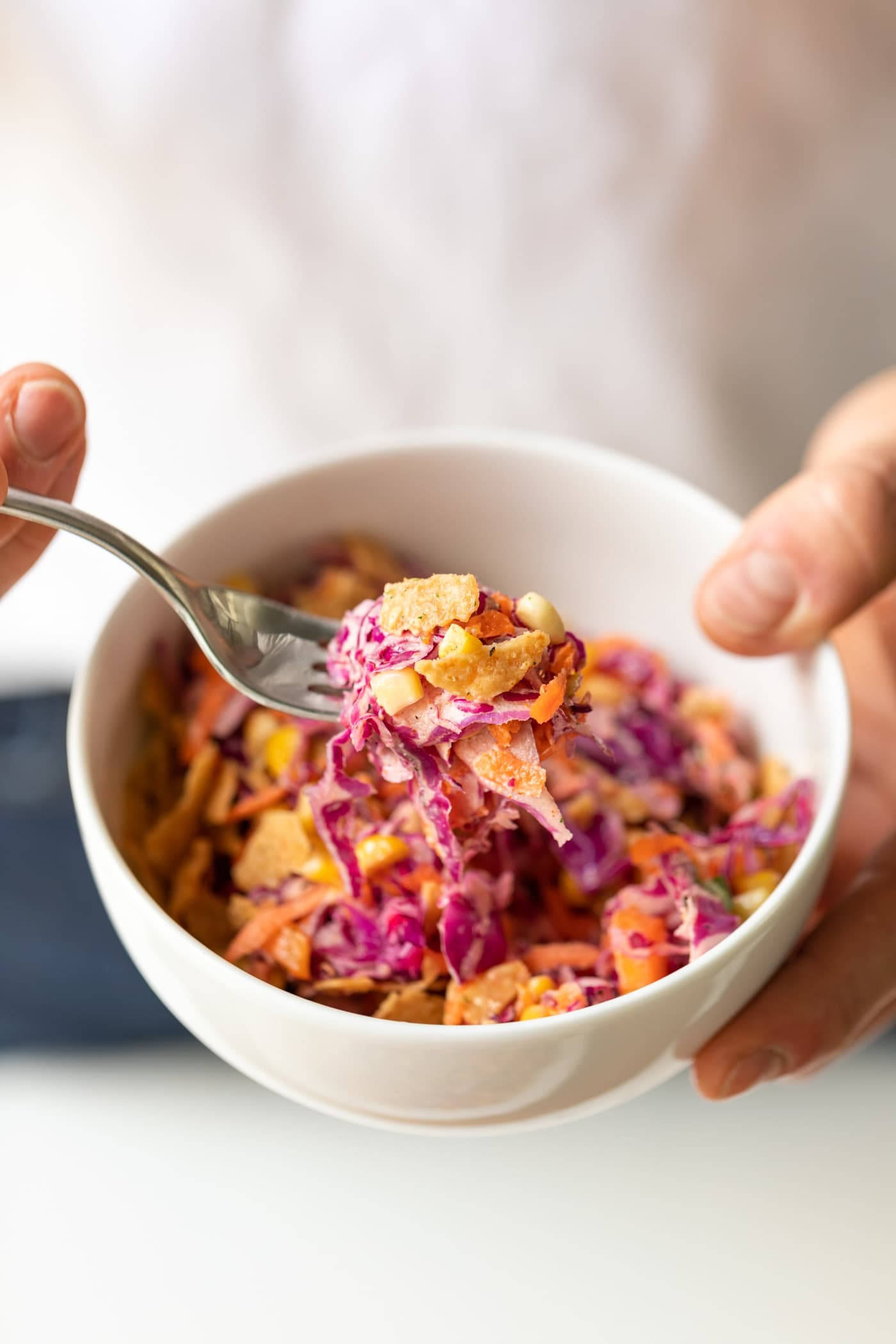 Two hands holding bowl filled with coleslaw made from red cabbage with fork holding bite