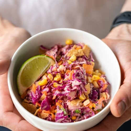 Two hands holding white bowl filled with Tex-Mex coleslaw made with red cabbage served with a lime wedge and topped with tortilla chips