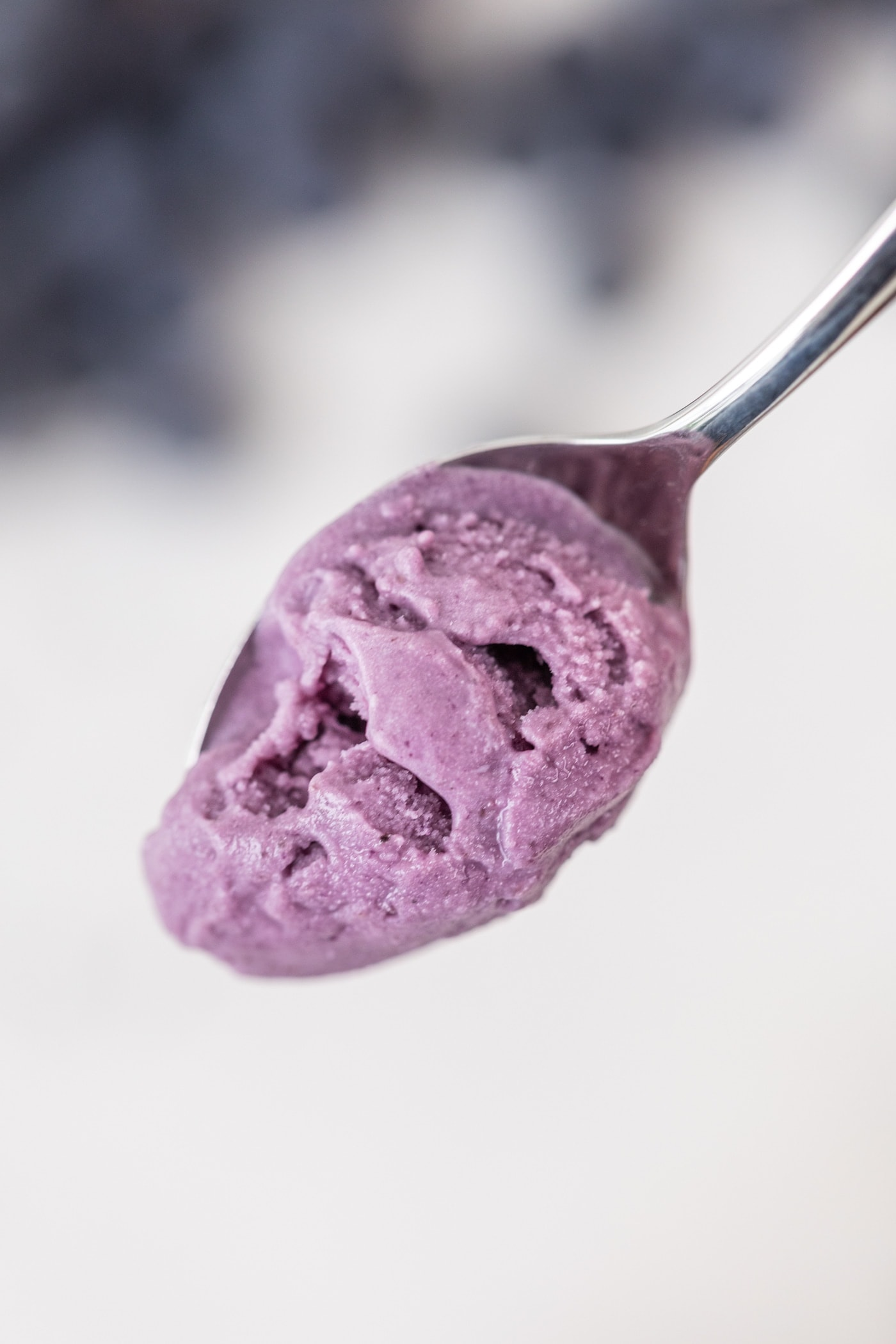 Spoon full of blueberry lavender ice cream with blurry blueberries on marble surface in background