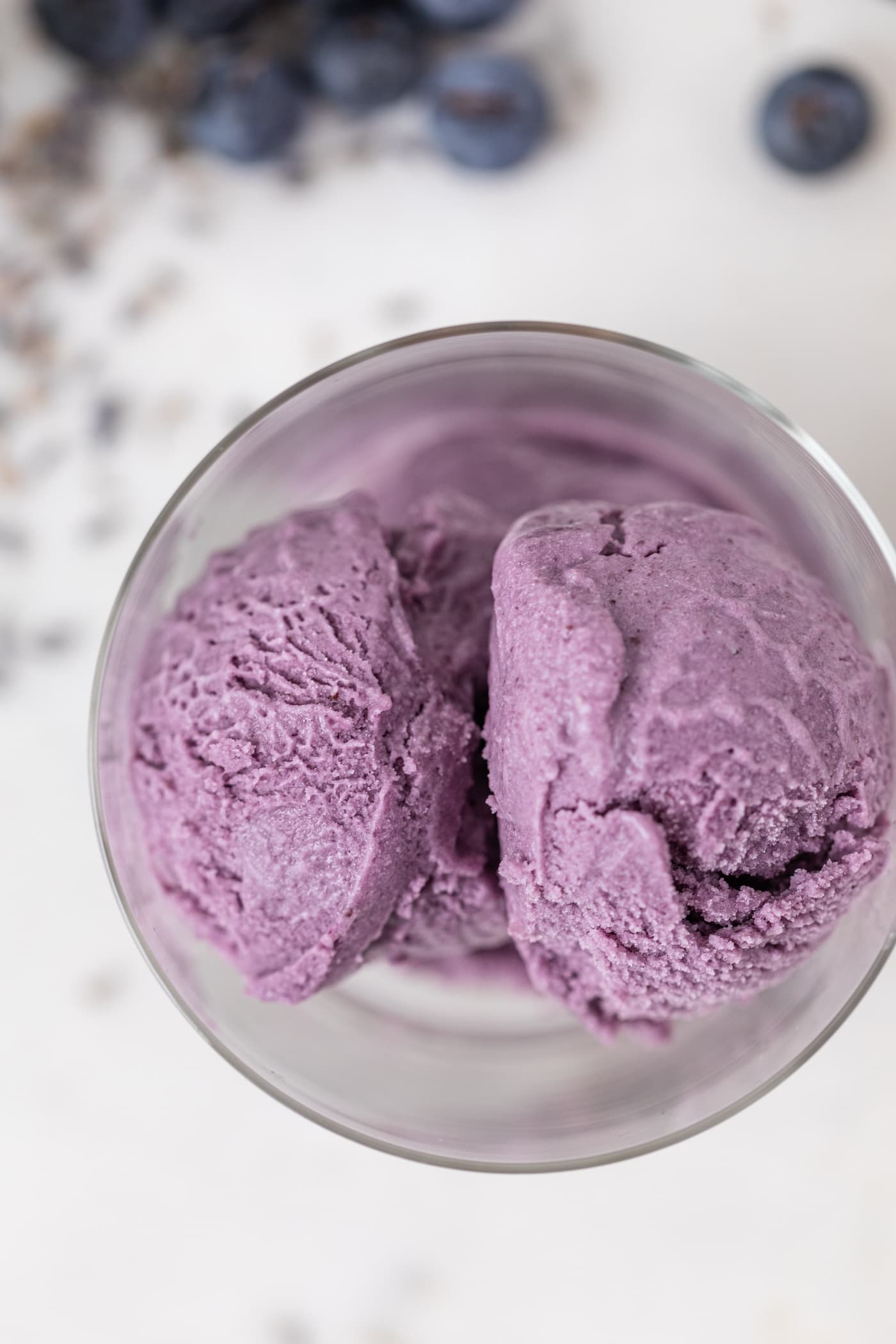 Top down view of purple ice cream in glass container with blueberries and dried lavender on marble surface