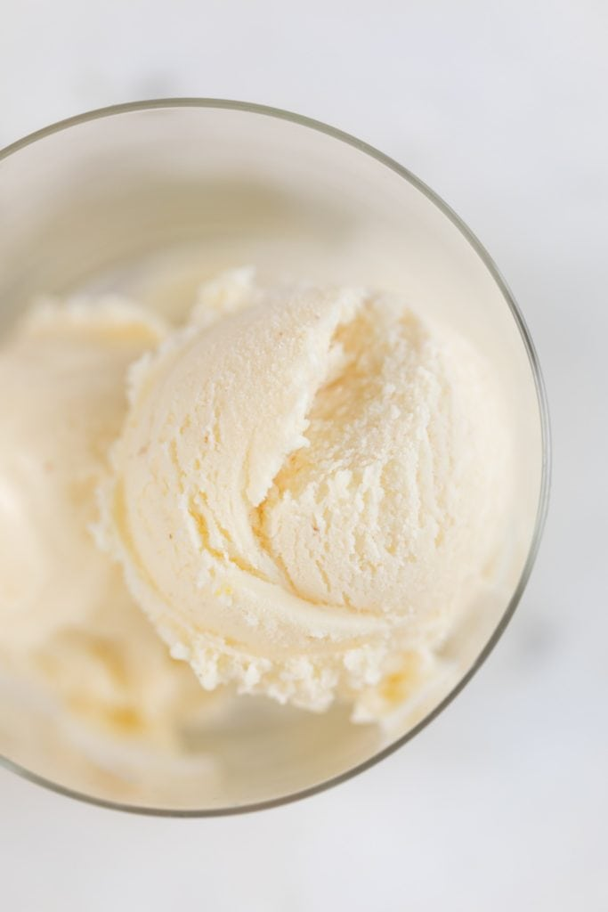 Top down view of orange sage ice cream sitting in glass container on marble surface