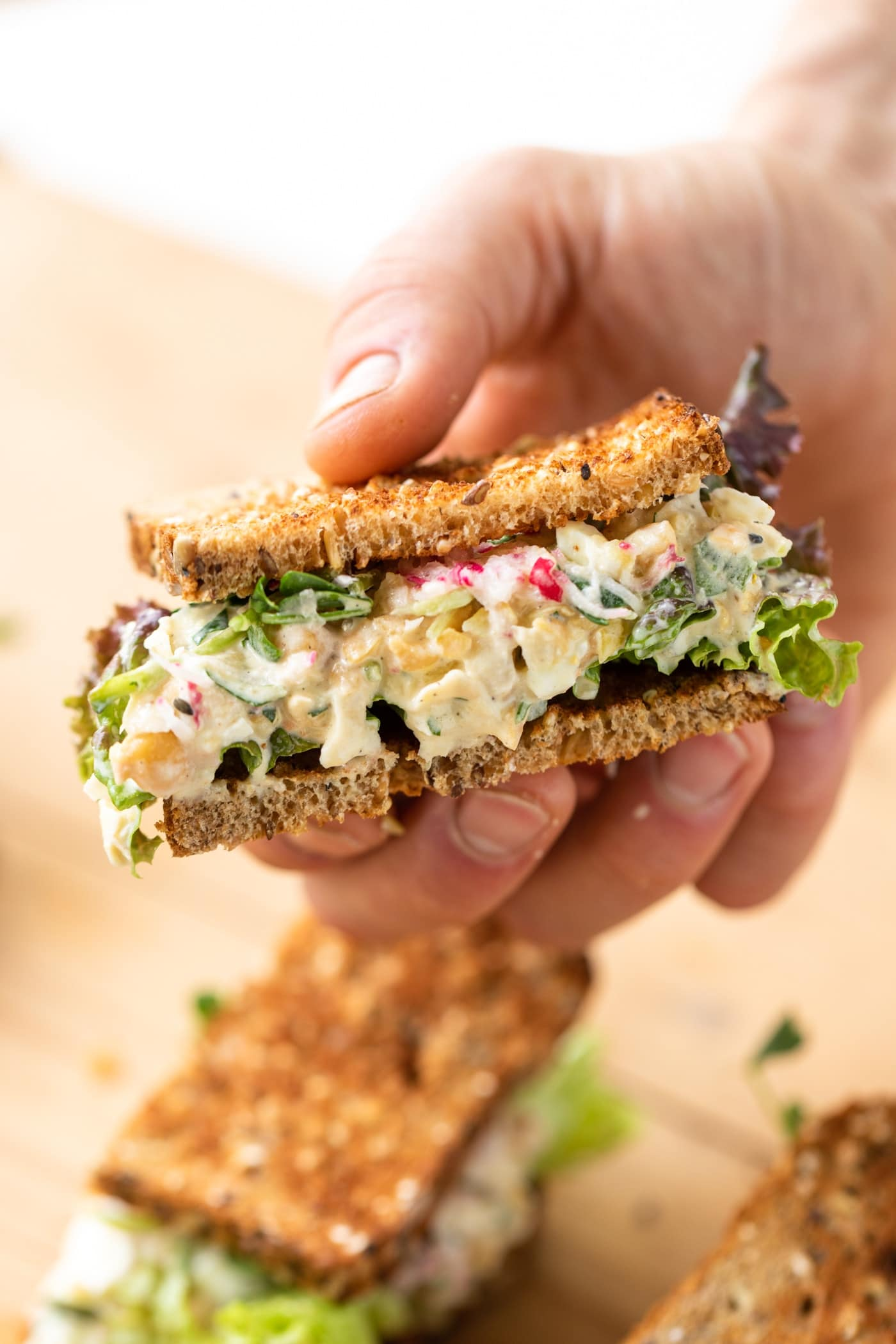 Hand holding a sandwich filled with chickpea salad and topped with lettuce and radish with extra half of sandwich sitting on wood board in background