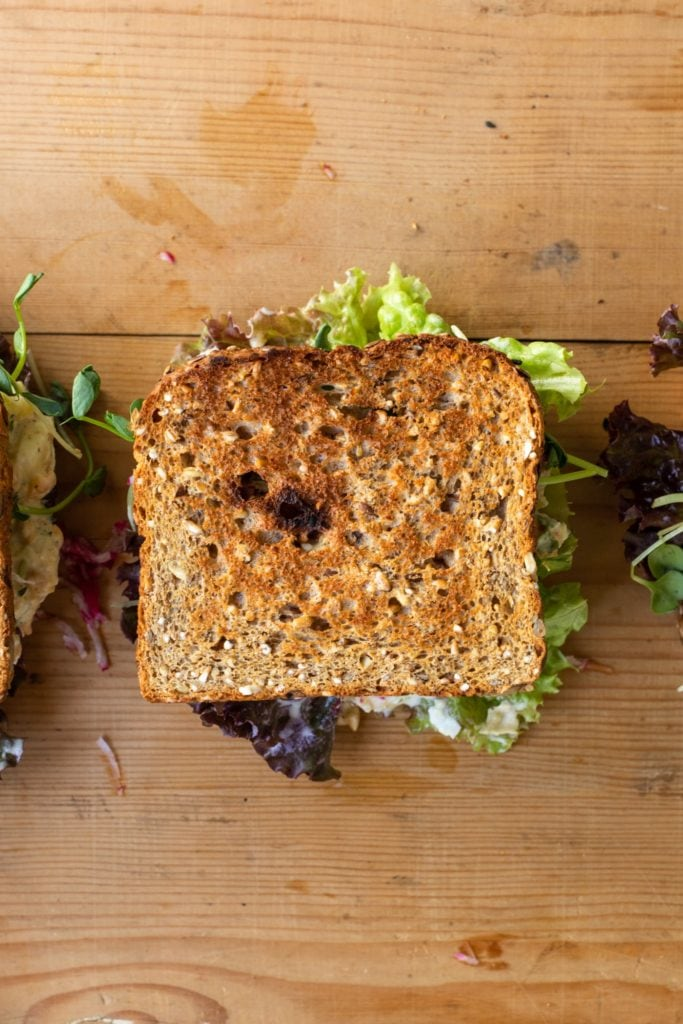 Top down view of sandwich with lettuce and chickpea sitting on wood board
