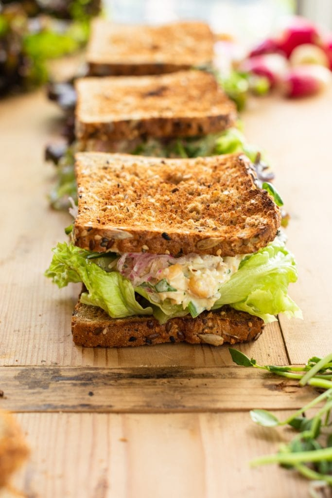 Chickpea salad sandwiched in between two toasted pieces of bread with lettuce and radishes sitting on wood board with extra sandwiches in background