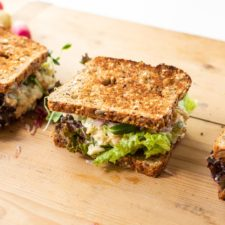 Wood cutting board with three sandwiches made from toasted bread with chickpea salad filling and lettuce with radishes in background