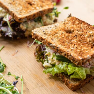 Wood cutting board with two toasted sandwiches filled with lettuce and chickpea salad with radish in background