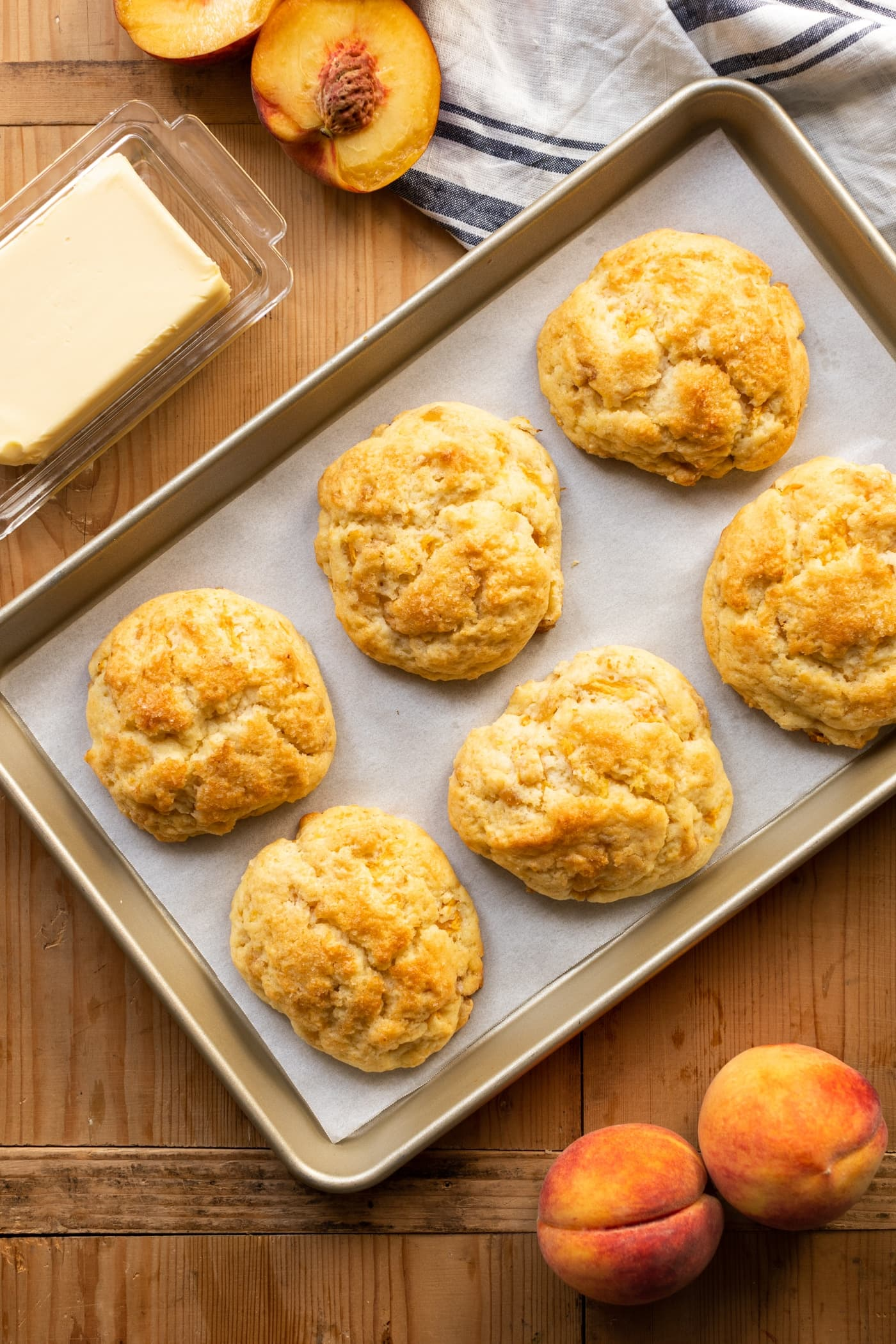 Top down view of peach drop biscuits cooling on piece of parchment paper in a baking tin with butter and sliced peaches in background all on wooden surface