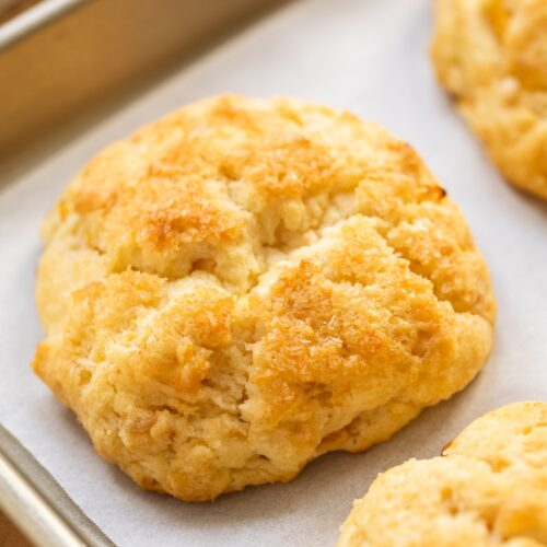 Golden brown biscuit sitting on piece of white parchment paper in a cooling rack all on wooden surface