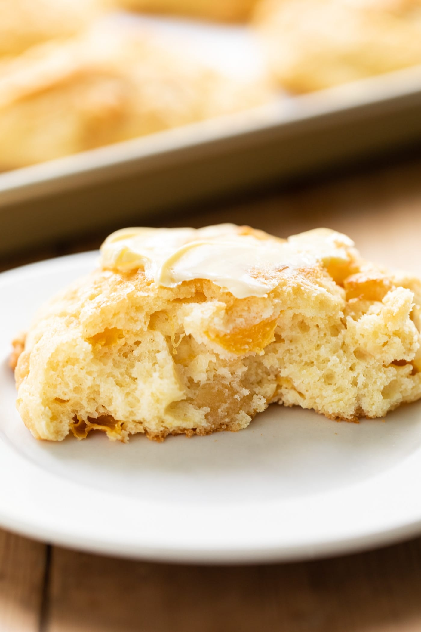 Peach drop biscuit cut in half with center exposed slathered with butter on white plate with extra biscuits on baking sheet in background all on wooden surface