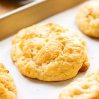 Peach drop biscuit sitting on piece of white parchment on baking sheet with wood surface in background