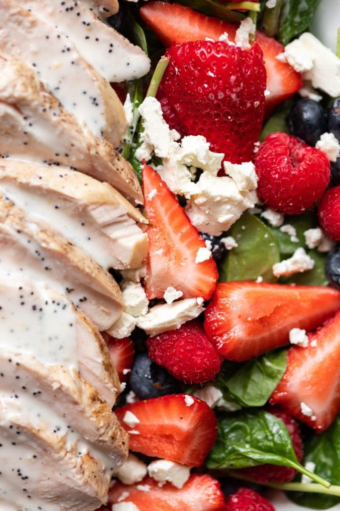 Pieces of strawberry and whole raspberries sitting on bed of spinach sprinkled with feta and layered with grilled chicken topped with lemon poppy seed dressing