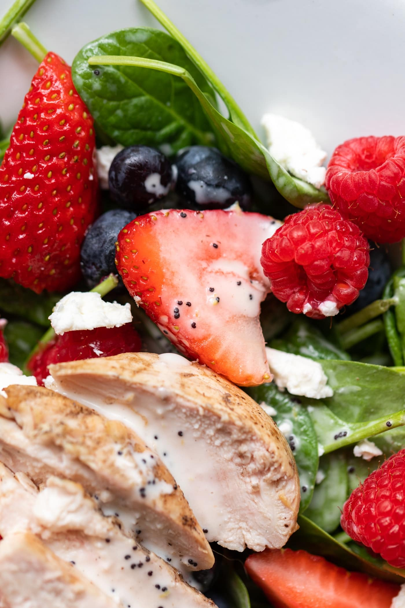 Half piece of strawberry and raspberries and blueberries sitting on spinach with grilled chicken all on white serving platter