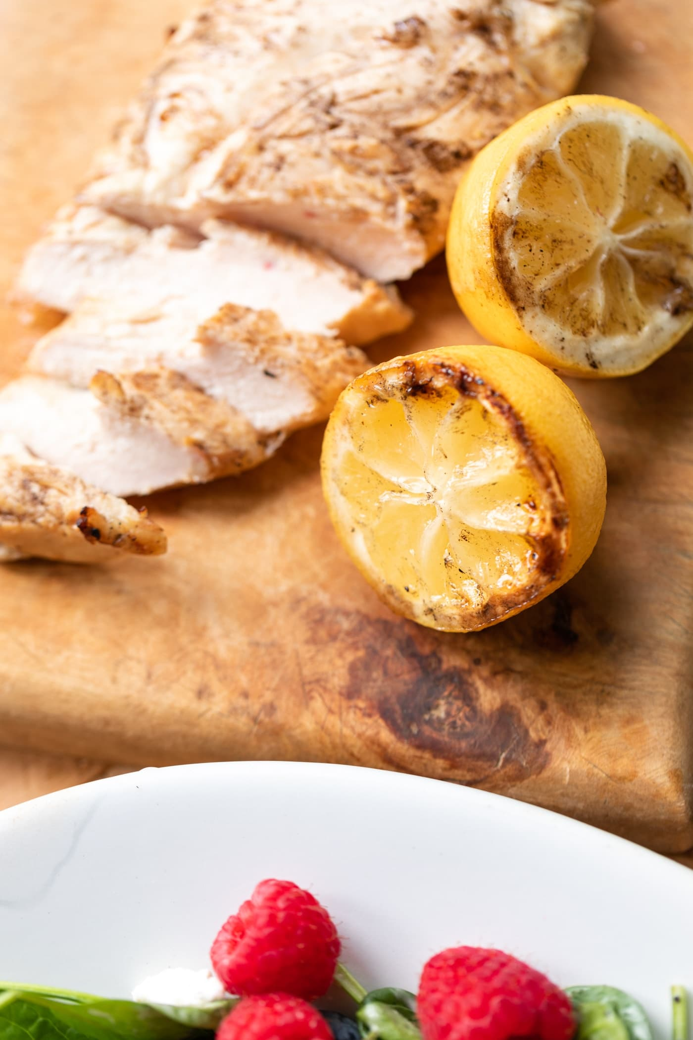 Used lemons sitting on wood cutting board with sliced chicken