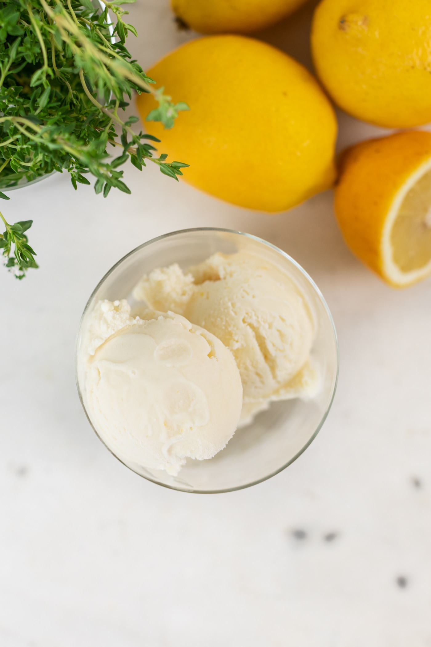 Top down view of lemon thyme ice cream in glass container with lemons and thyme in background all on marble surface