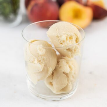 Glass full of three scoop of peach rosemary ice cream with extra peaches and rosemary in background all on marble surface