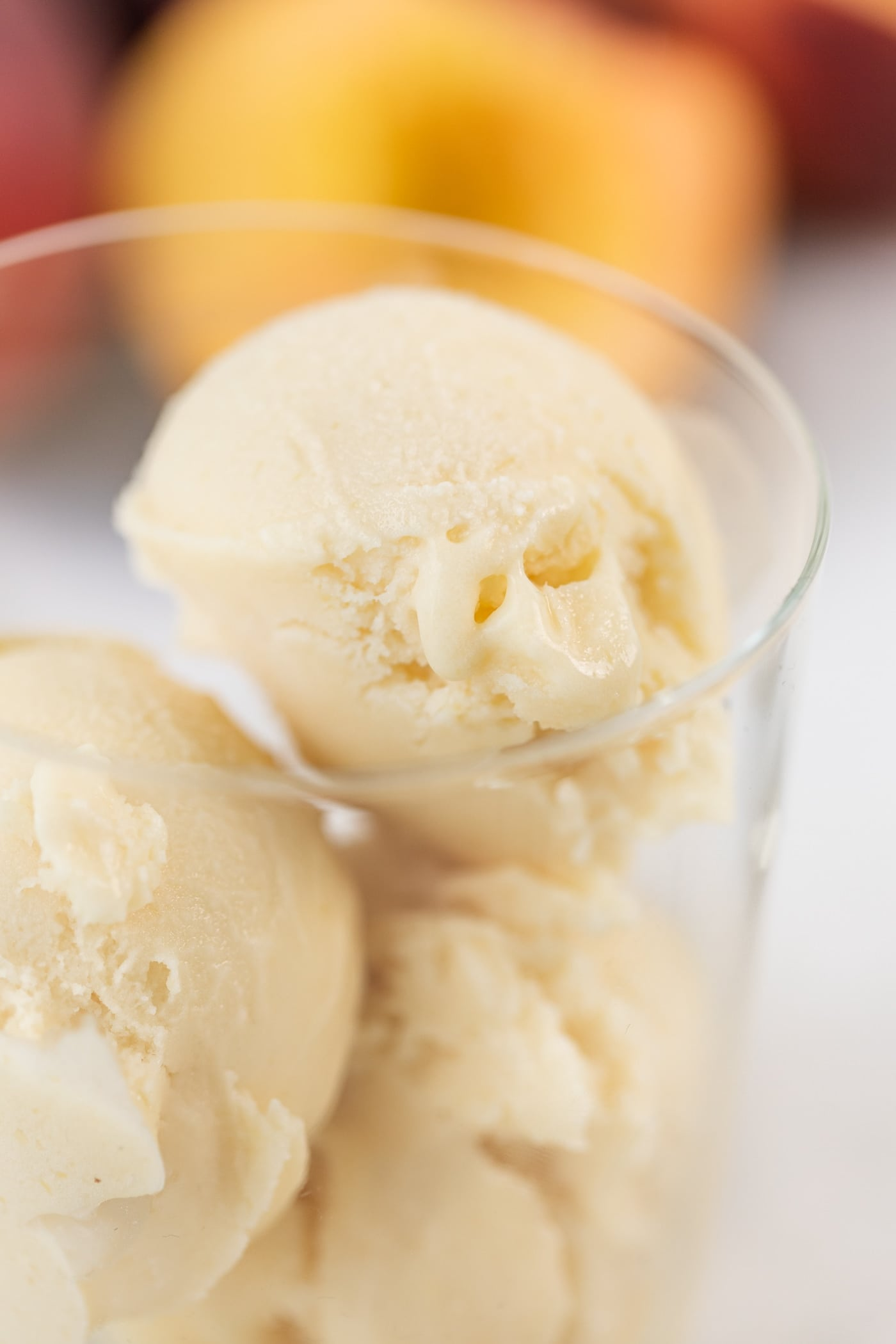 Close up view of light yellow scoops of ice cream sitting in glass with peach slices in background all on marble surface