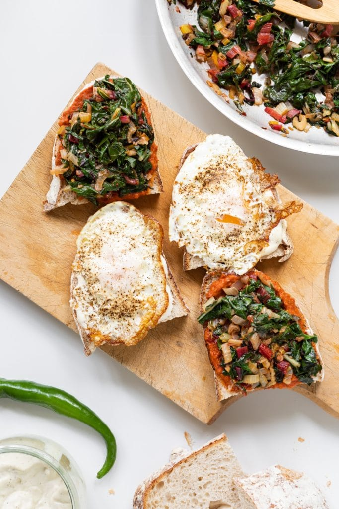Top down view of open faced sandwiches topped with fried eggs and Swiss chard mixture sitting on wood cutting board with extra pieces of bread all on white surface