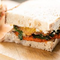 Swiss chard and harissa egg sandwich layered with homemade aioli sitting on wood cutting board with white background