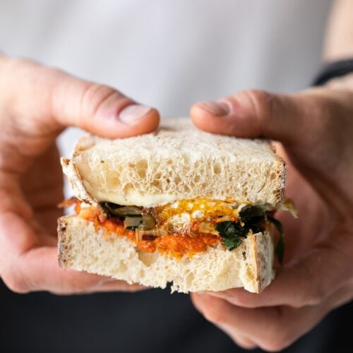 Two hands holding half of harissa egg sandwich topped with Swiss chard with white shirt and jeans in background