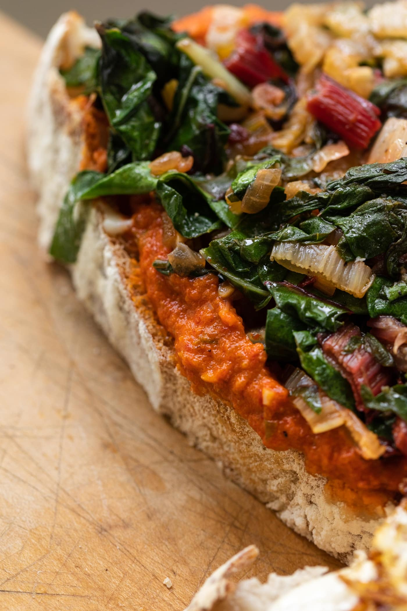 Harrisa sauce on piece of sourdough bread topped with Swiss chard mixture sitting on wood cutting board