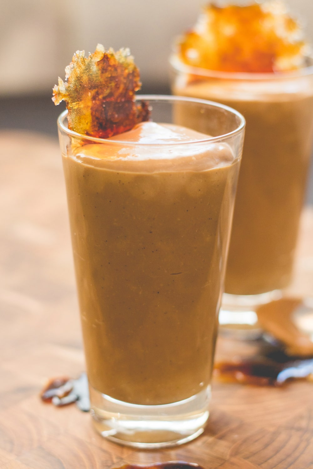 Tall glass filled with butterscotch pudding with browned piece of sugar on top all on wood cutting board surface