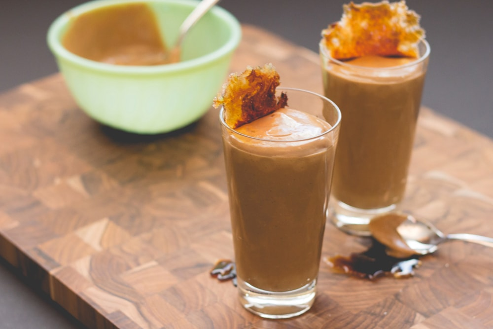 Tall glass filled with brown colored pudding with browned sugar crisp on top with light green bowl sitting in background all on wood cutting board surface