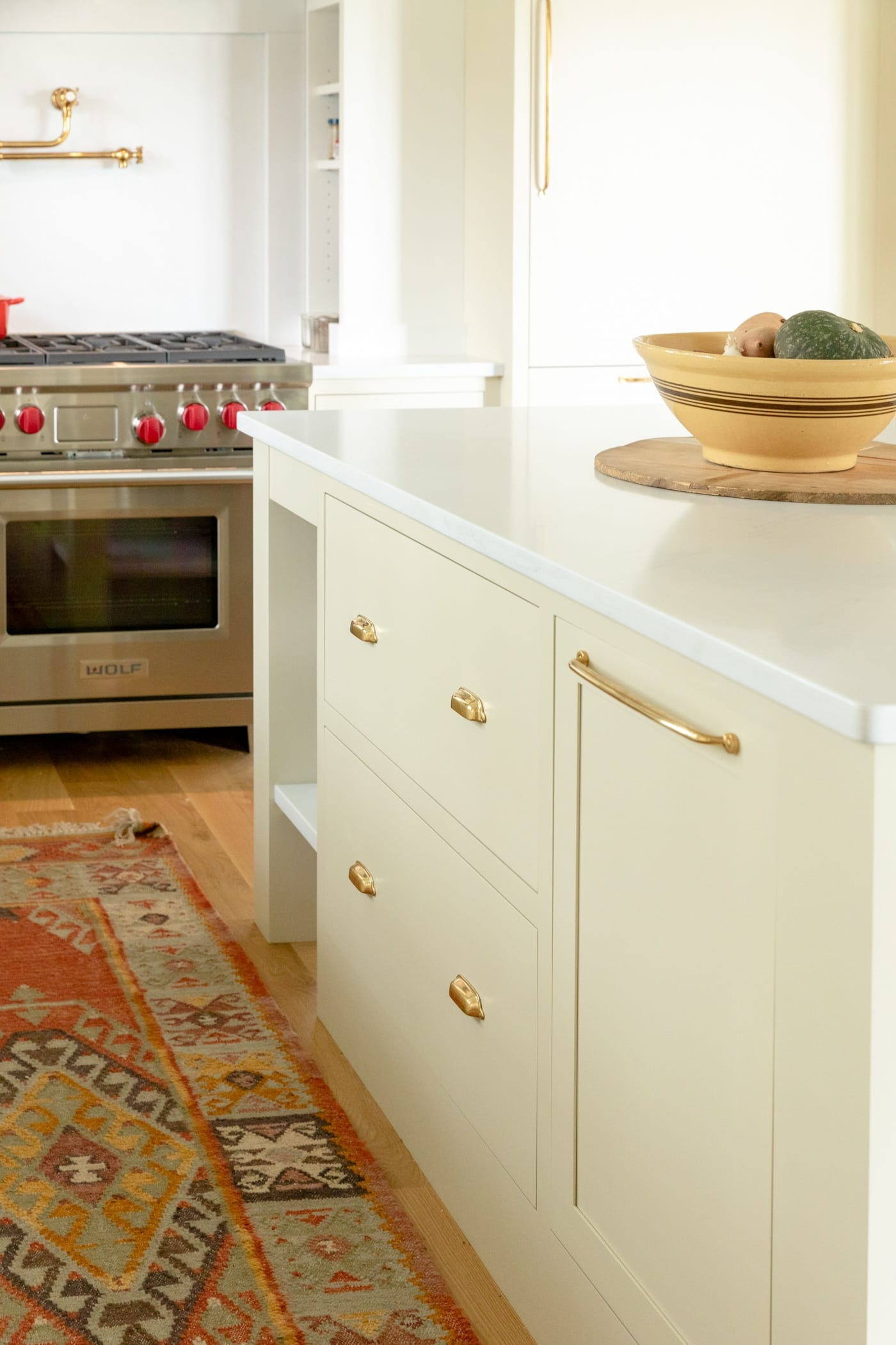 Large drawers in a kitchen island with range in background and red rug on hardwood floors