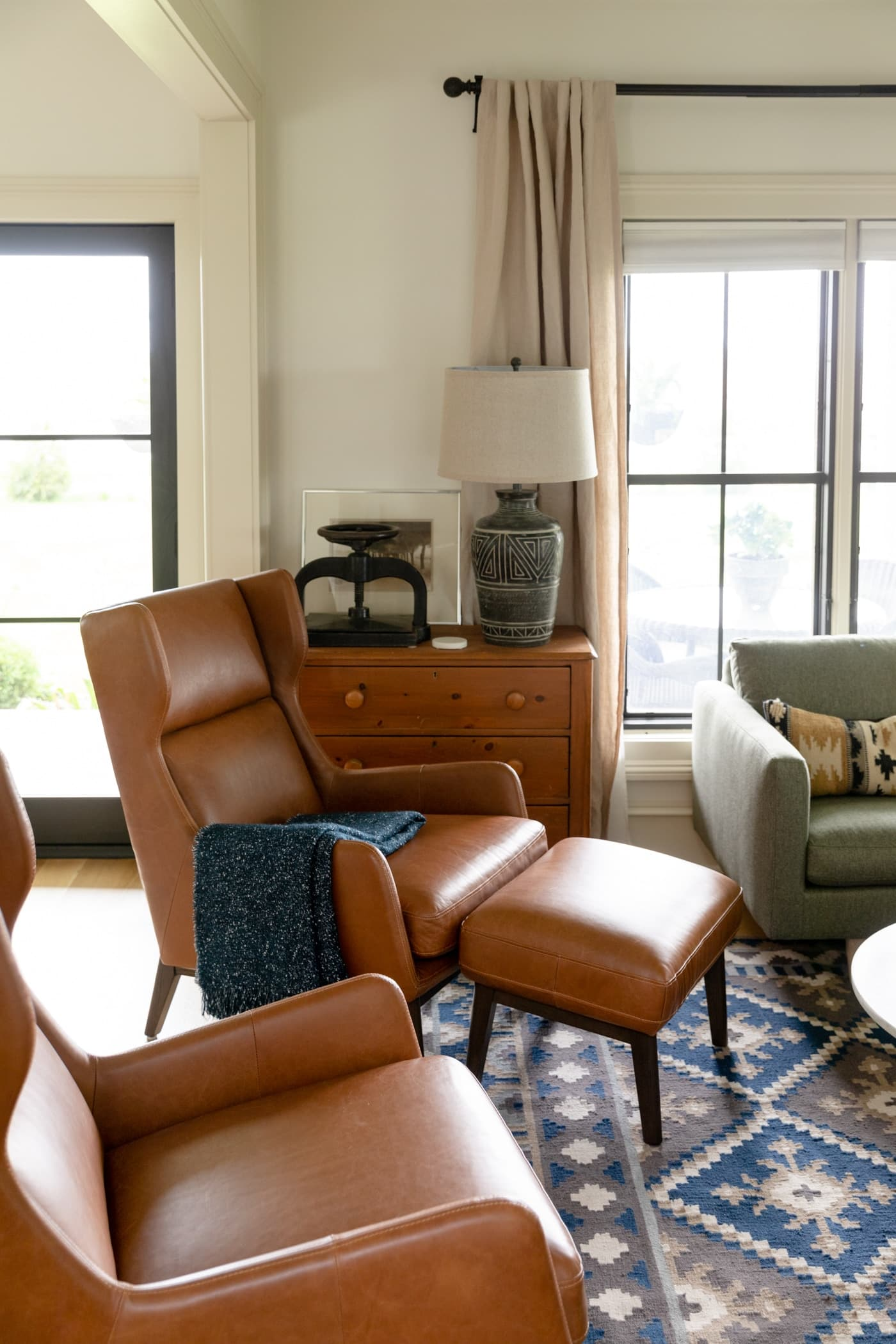 Two brown leather chairs sitting on blue colored rug with pine chest and black French door in background