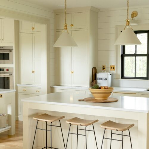 Kitchen stools sitting at a large island in a farmhouse kitchen with black windows and pantry cabinet in background