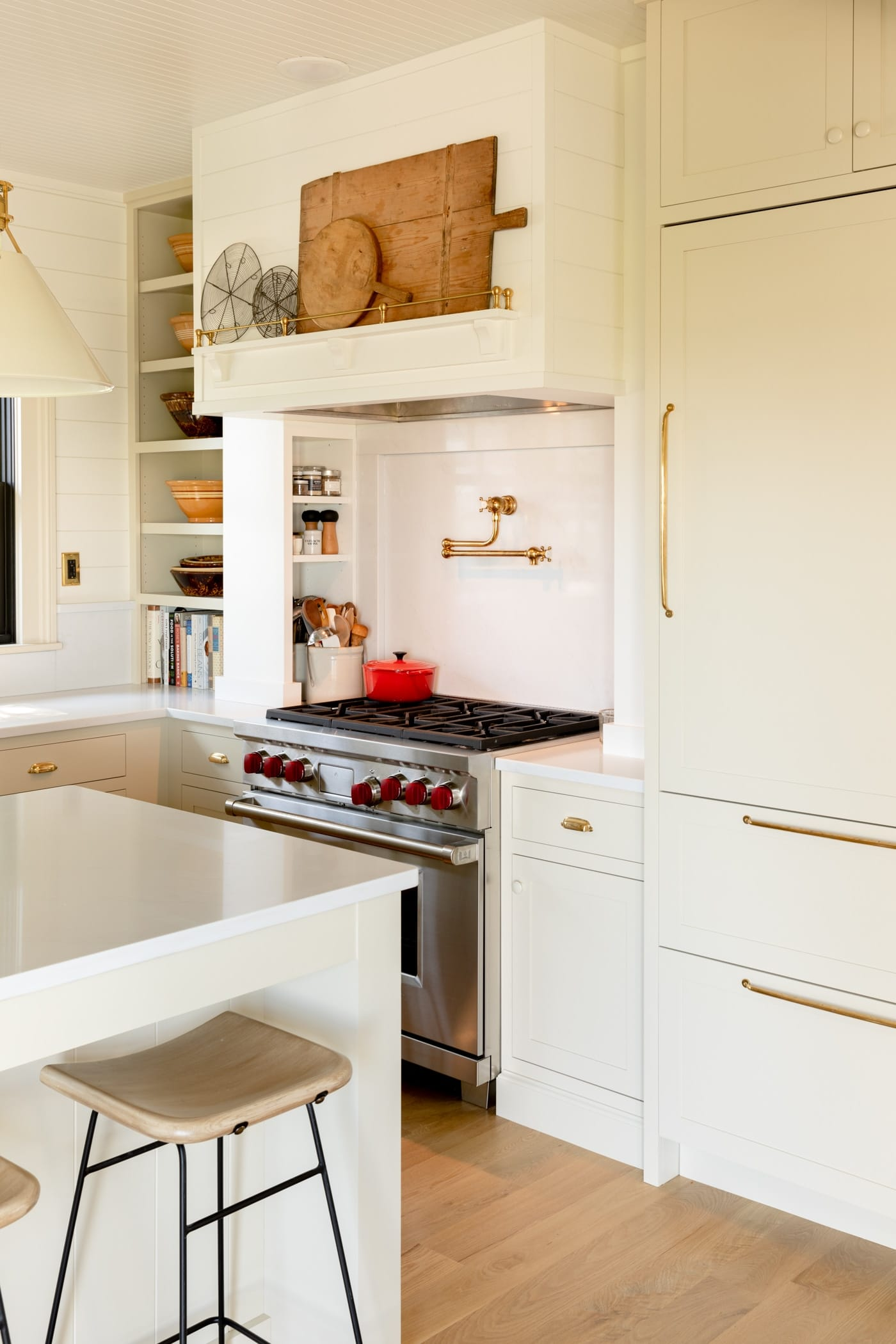 Large stainless steel range with red knobs surrounded by cabinetry and vent above with cutting boards sitting on a wooden shelf