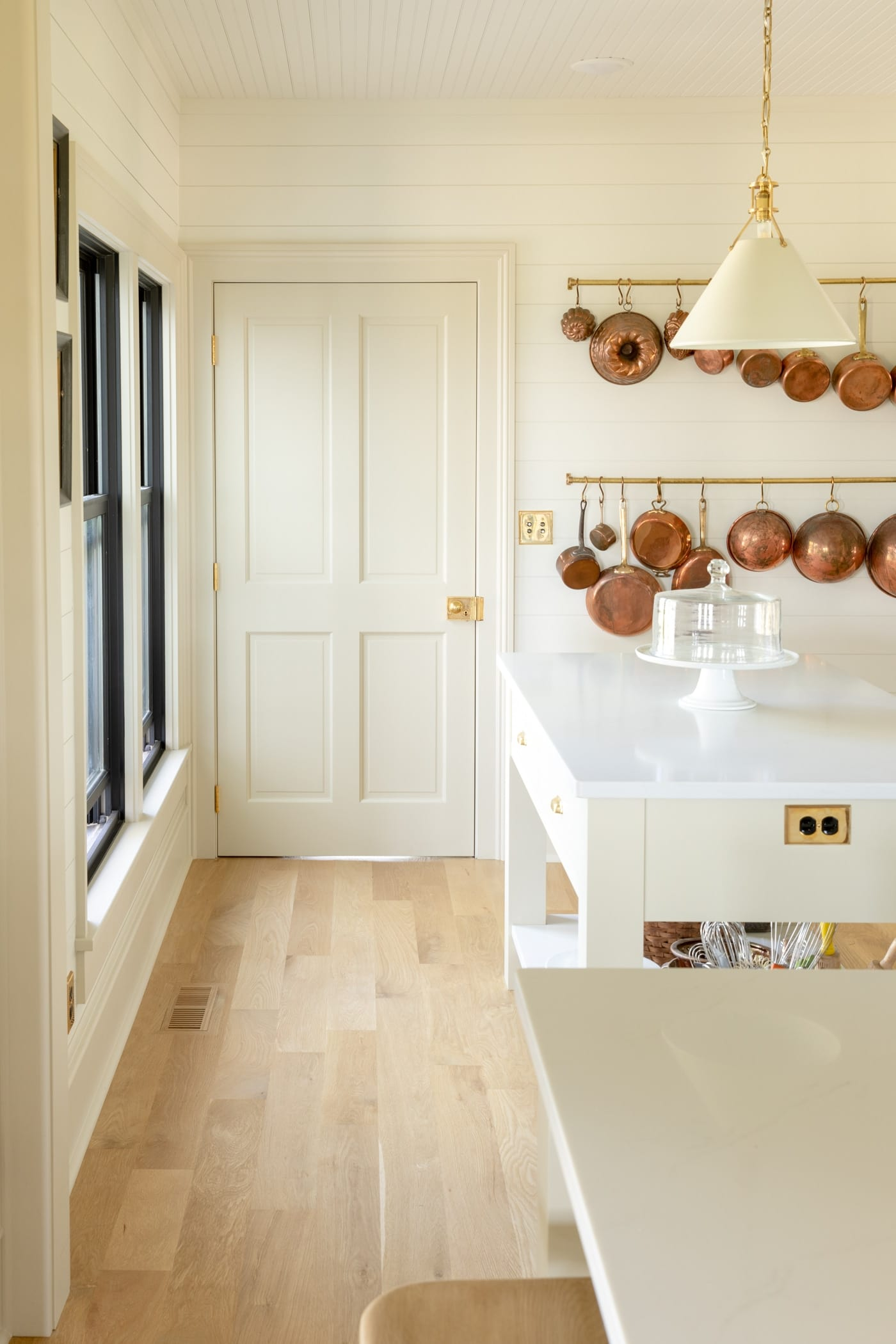 Four square creamy colored panel door with light oak floors leading up to it with small island to the side