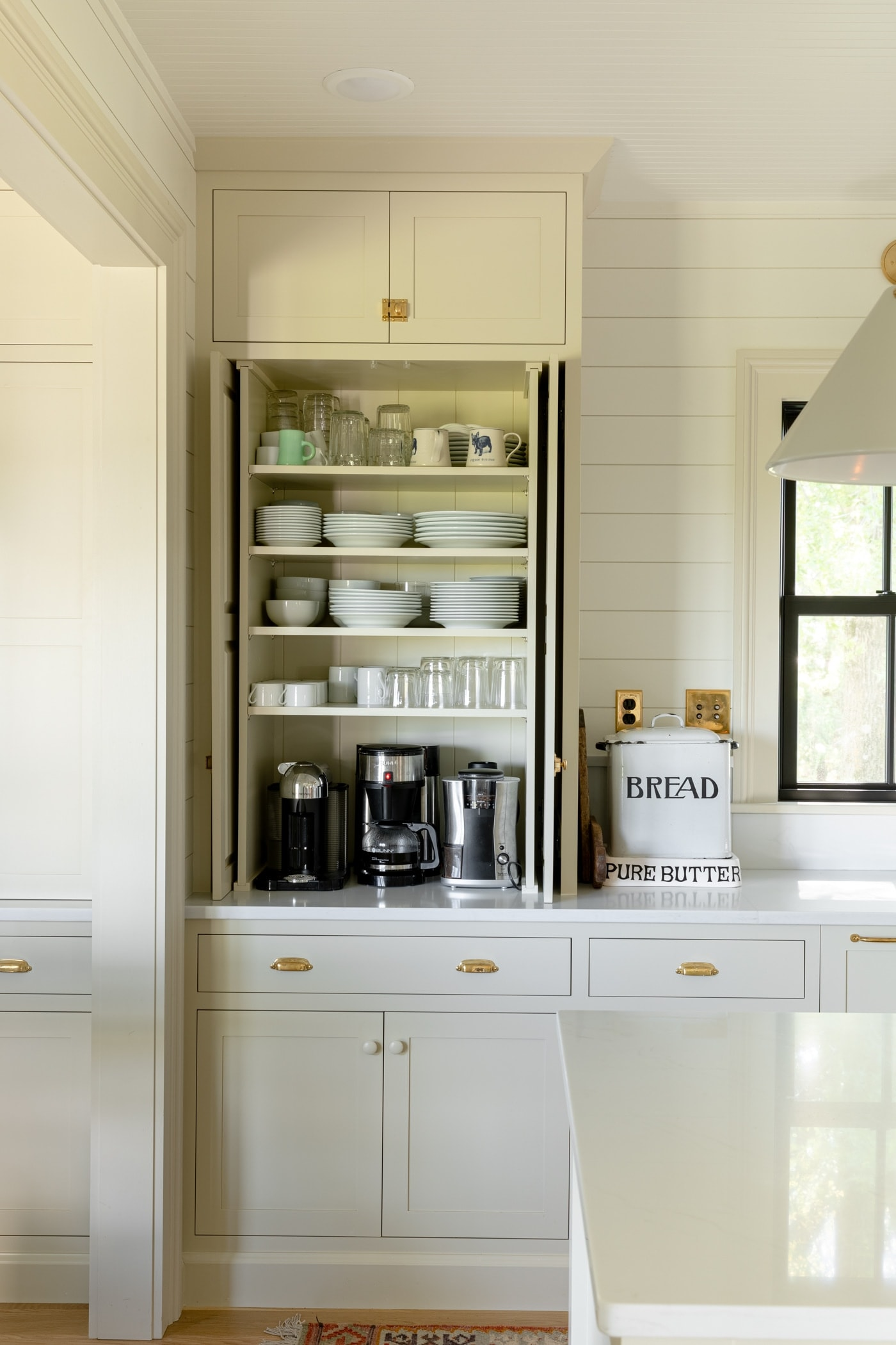 Large upper cabinet sitting on countertop with doors open revealing plates, mugs, bowls, and coffee maker