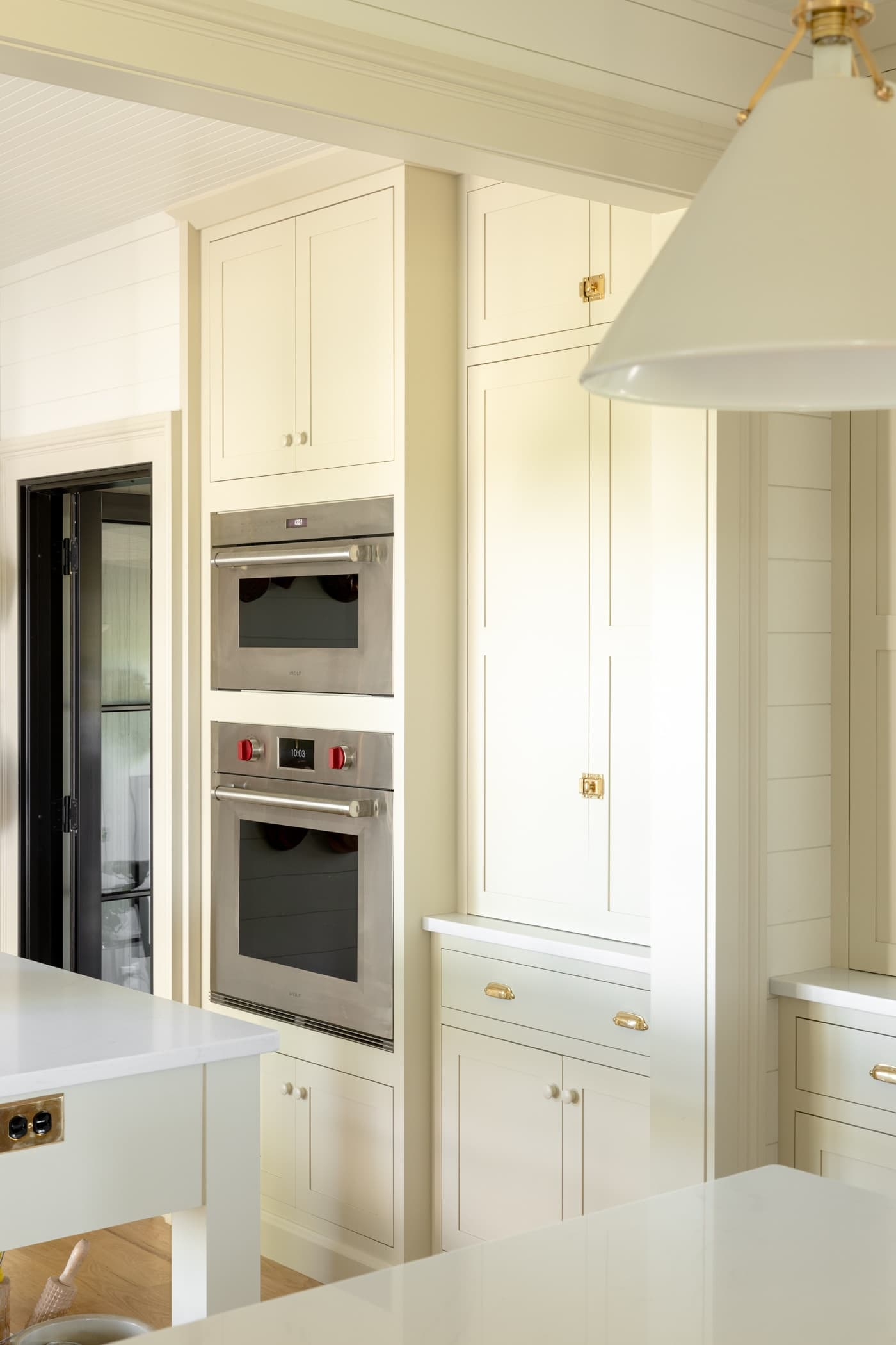 Wall oven in a creamy white cabinet with pantry cabinet right beside it with black door in distance