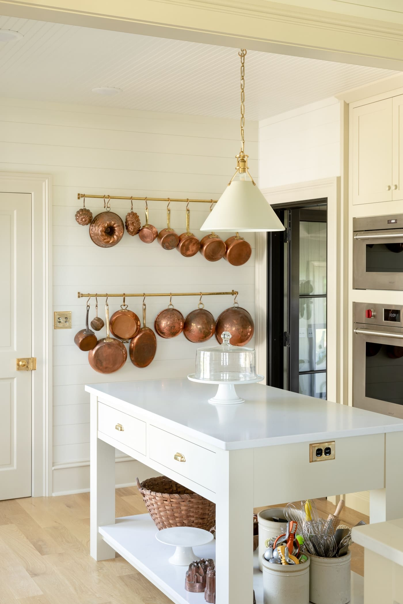 Small island with chunky legs and lower shelf covered in marble with wall oven behind and rack filled with copper cookware