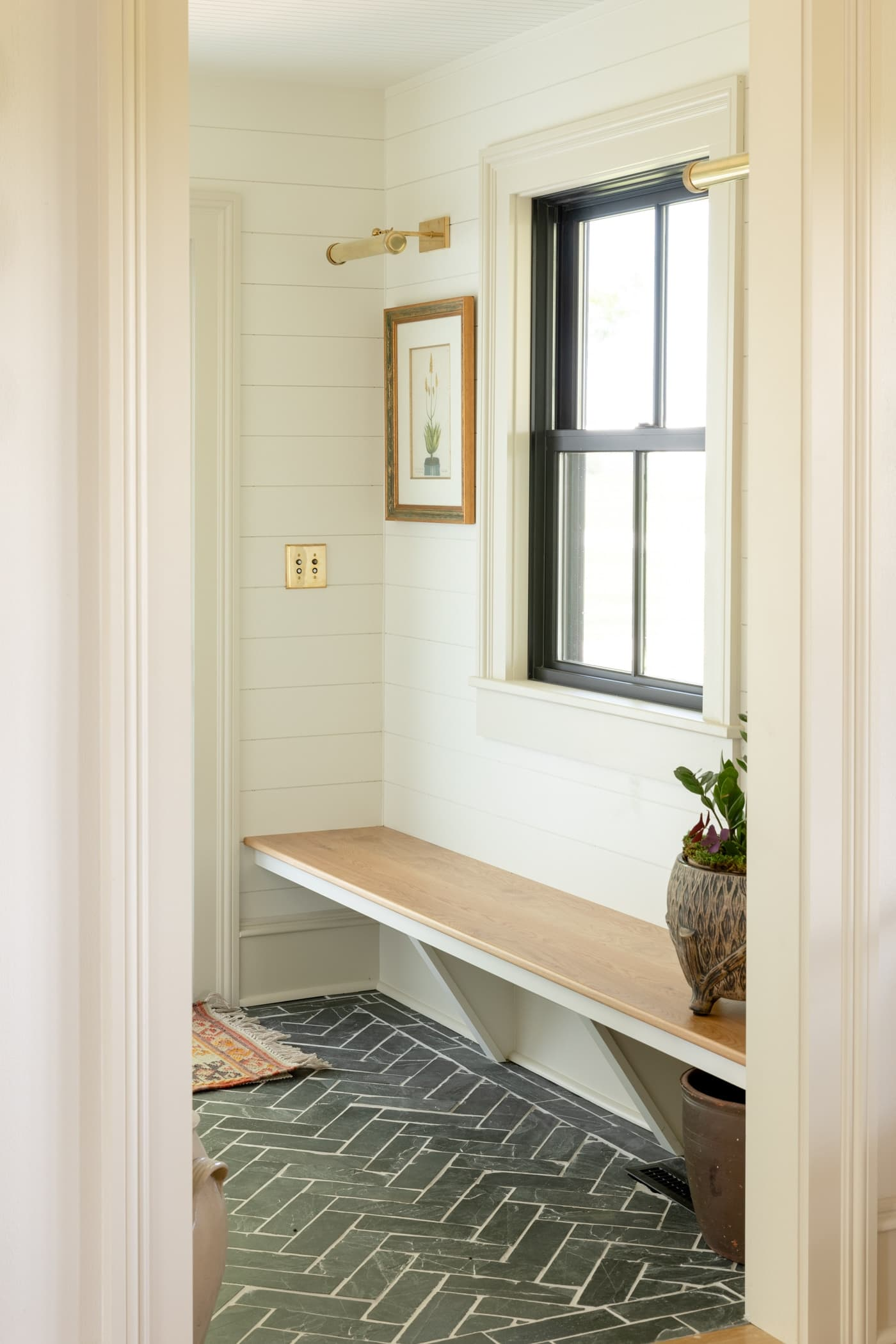 Dark gray slate floor and white oak bench make up a small entry space with black window and painting with a brass sconce above